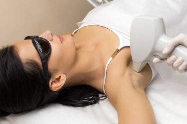 Laser hair removal in professional beauty studio. Beautician in white sterile gloves make the procedure on the client's armpit.